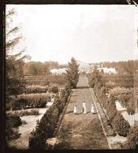 Image of Garden view looking north from observatory.  Women visible on path leading to the Main Conservatory.