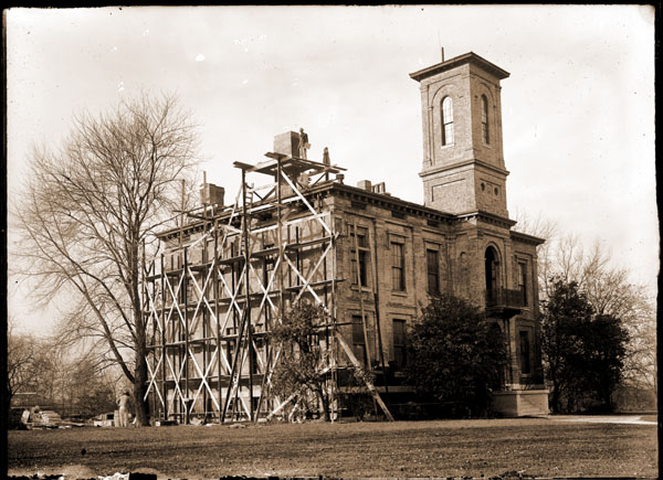 Image of Tower Grove House being stuccoed. (shows scaffolding). Horizontal orientation. 1- 5x7 in. print.