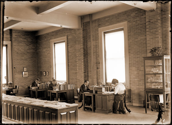 Image of Administration Building interior.  Showing the Herbarium/Library Study Room. Graduate students from the Henry Shaw School Of Botany.  2nd from right; Jacob R. Schuamm.  NEGATIVE AVAILABLE -- SEE PML 1980-0660, and PRINT AVAILABLE -- SEE PHO 1980-0660 and PHO 2007-0276.