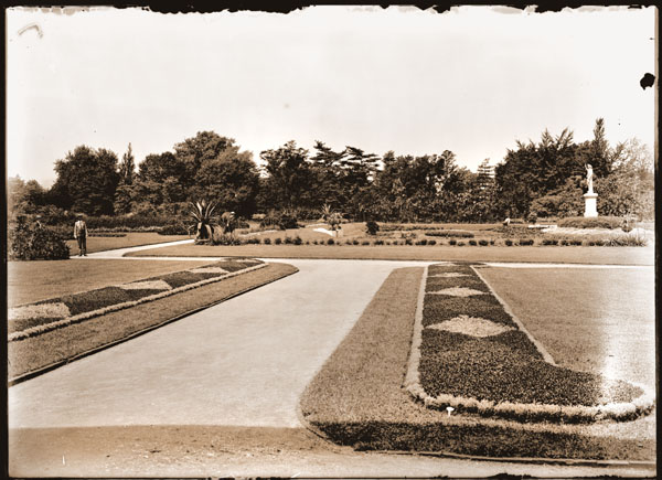 Image of View of carpet bedding at Main Gate.  View is directly west with Juno at right. Visitors visible to the left.  (Gardener & 2 ladies.)