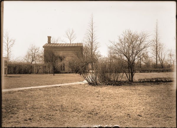 Image of Tool shed in vegetable garden south of Shaw's country home.  View is of East side of building.  Greenhouse originally at south end of building is gone.