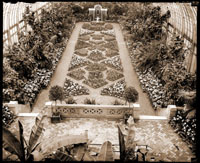 Image of Spring Flower Show. View of patterned beds from upper level. Statue of boy holding fish at north end.  5x7 in. print of slightly different view.