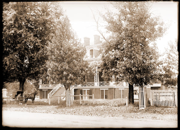 Image of The Casino, surrounded by trees with horse-drawn carriage on dirt road.  The Casino was located where the Director's Residence now stands.  One 5x7 in. black and white print.  PRINT AVAILABLE -- SEE PHO 1983-0345.