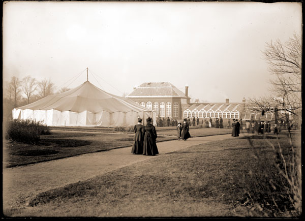 Image of Main Conservatory with tent set up in front.  Ladies strolling along the path.  View is to the north.  5x7 in. black and white print.  PRINT AVAILABLE -- SEE PHO 1983-0346.