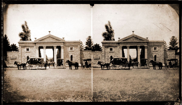 Image of Main Gate with carriages lined up on street.  Stereograph.  PRINTS AVAILABLE -- SEE PHO 1983-0464, PHO 2006-2451, PHO 2006-2452, PHO 2006-2453, PHO 2006-2481 and PHO 2006-2489.  Negatives available at PHO 2006-2468, PHO 2006-2490, PHO 2006-2505 and PHO 2006-2506.  Gateway Heritage, pg. 25.  Summer 1984.