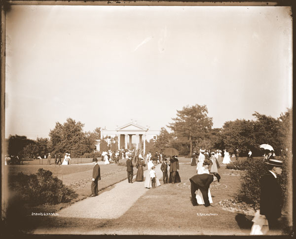 Image of View inside of the Garden parterre with many visitors viewing plantings.  View is to the east with the Main Gate in background.  PRINT AVAILABLE -- PHO 1982-0008.