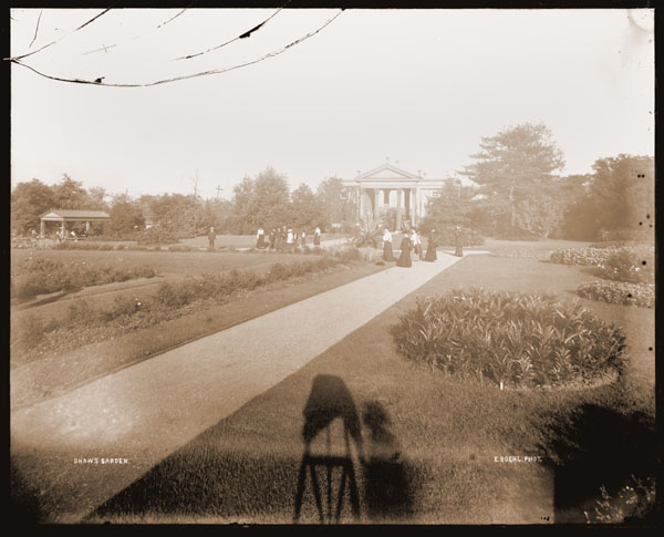 Image of View from inside the Main Gate.  Garden with people on east/west & north/south paths.  Rectangular gazebo at left.  Shadow of photographer and camera can be seen in foreground.