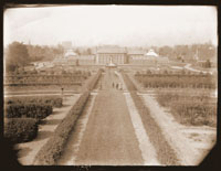 Image of View of the Main Conservatory (1868-1916)  probably taken from the Observatory.  Ladies in the foreground.  Person can be seen running just in front of Juno.  Person appears as a blur due to the slow exposure rate of the camera.