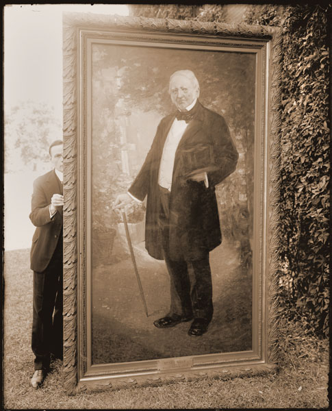 Image of Henry Shaw portrait being held upright by George T. Moore.  The 1906 oil painting is by Richard E. Miller.