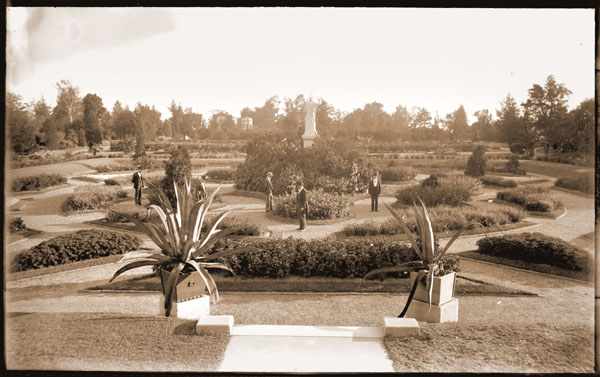 Image of View of the parterre with gentlemen on paths.  Juno is in center.  Victory and museum can be seen in background.  View is looking south from the steps of the Main Conservatory.