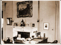 Image of Fireplace, desk, framed picture on wall.
