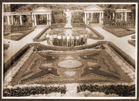 Image of MBG Italian Garden (a.k.a. the Formal Garden).  Employees posed for group shot in center of garden with Juno statue, Arbor in background.  Adhered to scrapbook page with another photograph on reverse side.  The Pergola was the open row of columns and trellises bordering the west side of the Italian Garden.  The Arbors were the two roofed structures at the center of the Pergola.  The Greenhouse which made up the surrounding border of the Italian Garden was -- as a whole -- referred to as the Conservatory or the Italian Garden Greenhouse, with each part of the building segmented into; Desert House, Cycad and Fern House, Economic House, South African House, and Palm House.  After the Palm House was torn down, the remaining south and north buildings were called the Desert House and the Mediterranean House.