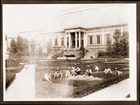 Image of MBG Italian Garden (a.k.a. the Formal Garden).  Employees posed for group shot in front of Conservatory.  Adhered to scrapbook page with another photograph on reverse side.  The Pergola was the open row of columns and trellises bordering the west side of the Italian Garden.  The Arbors were the two roofed structures at the center of the Pergola.  The Greenhouse which made up the surrounding border of the Italian Garden was -- as a whole -- referred to as the Conservatory or the Italian Garden Greenhouse, with each part of the building segmented into; Desert House, Cycad and Fern House, Economic House, South African House, and Palm House.  After the Palm House was torn down, the remaining south and north buildings were called the Desert House and the Mediterranean House.