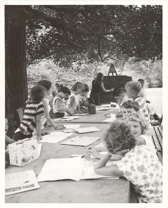Image of Children learning about plants under the widespreading branches of a hundred year old gingko.  Carol Kohler, teenage apprentice, is teaching.  MBG Bull 54 (7): 21( Sept. 1966).  Negative available at PHO 2005-0883.