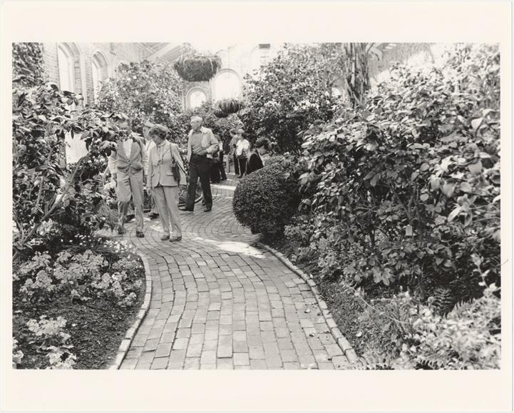 Image of Linnean House, interior.  Visitors on interior brick walkway.