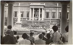 Image of View taken from the pergola showing part of crowd and the speakers dias behind the Palm House.  Italian Garden.
