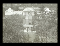 Image of View through the grove of the Observatory and the Main Conservatory from atop of Tower Grove House.  Ladies can be seen sitting in the upper level of the Observatory.  Linnean house is in the background.  View is to the north.