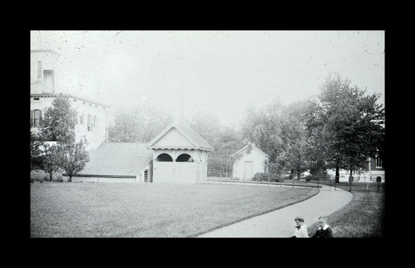 Image of Tower Grove House outbuildings and yard view. Two boys visible to the right, Tower Grove House to the left.  Museum visible in background.
