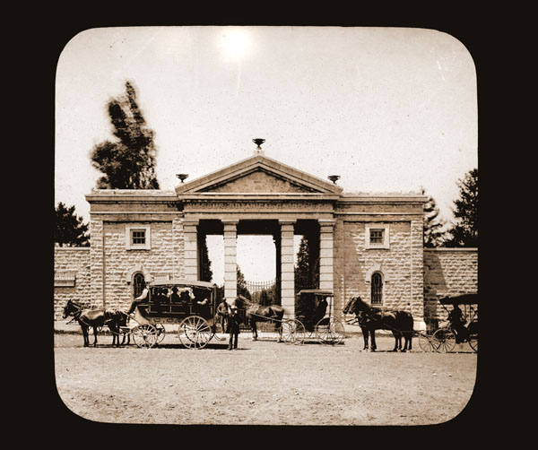 Image of Street side view of Main Gate.  Several horses and carriages visible.