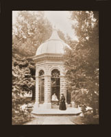 Image of Rebecca Edom, dressed in black mourning, standing beside the tomb, 1889.