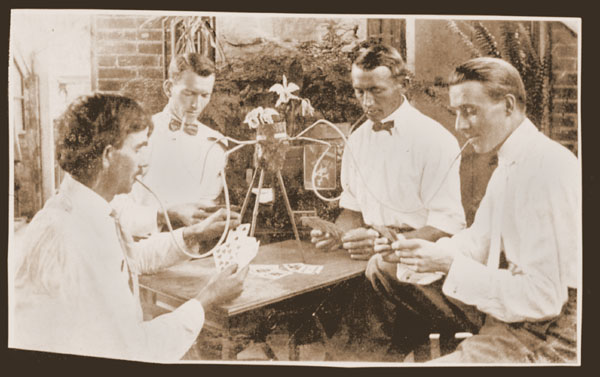 Image of Sepia slide of Pring and others smoking a pipe and playing cards ca 1910 Bulletin 51(2):5 Water Lily History by George Rogers in 1986. (22)